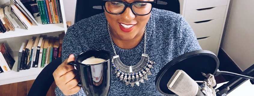 WOC Podcaster with a cup of joe talking social media.