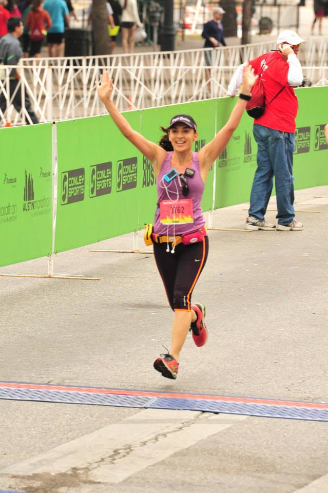 Podcaster Cepee Tabibian crossing the finish line at a marathon.